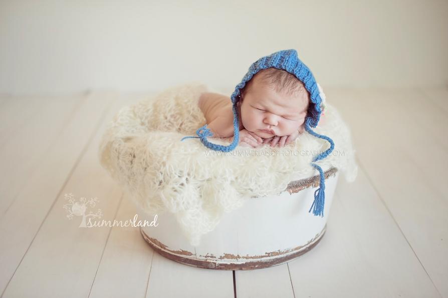 Summerland newborn girl in blue bonnet white wood floor Sunnyside
